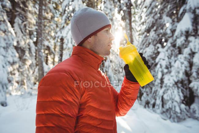 Человек пьет воду из бутылки в лесу зимой — стоковое фото