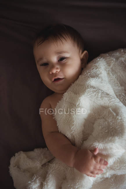 Bebê fofo deitado na cama em casa — Fotografia de Stock
