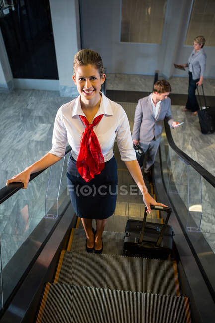 Female staff and passengers with luggage on escalator in airport — Stock Photo