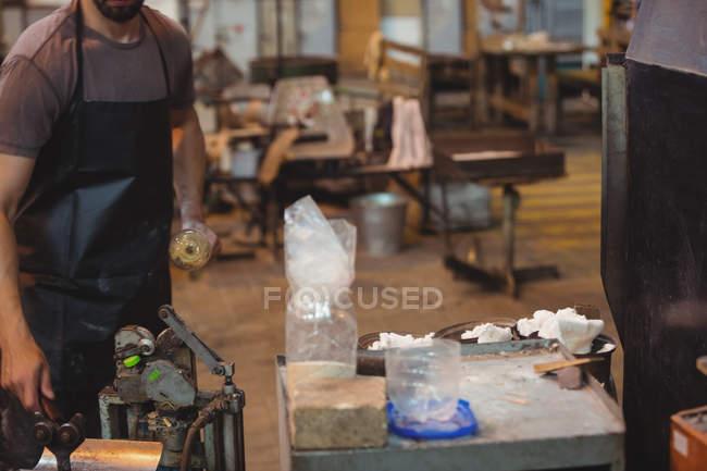 Section médiane du souffleur de verre tenant sarbacane et réglage de machine à l'usine de verre soufflé — Photo de stock