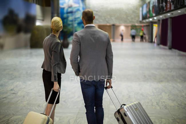 Вид сзади на деловых людей с багажом в терминале аэропорта — стоковое фото