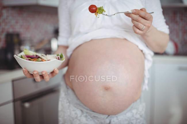 Средняя часть беременной женщины с салатом на кухне дома — стоковое фото