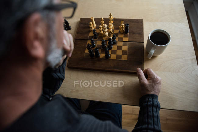Attentive man playing chess at home — Stock Photo