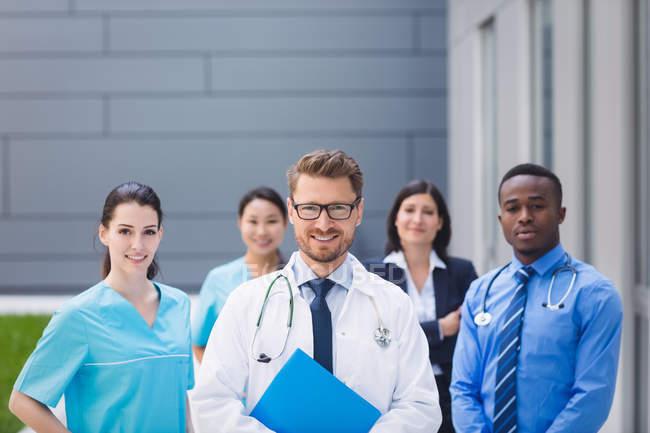 Портрет улыбающихся врачей, стоящих вместе в помещении больницы — стоковое фото