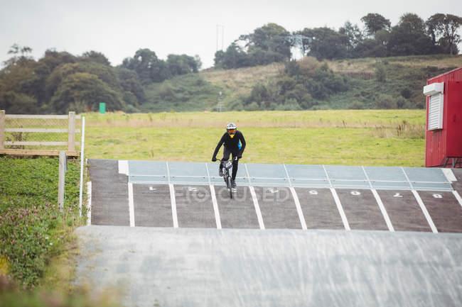 Велогонщик на велосипеде BMX на старте пандуса в скейтпарке — стоковое фото