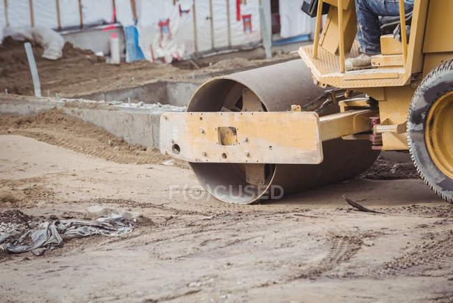 Низький розділ чоловік працює на будівельному майданчику бульдозер — стокове фото
