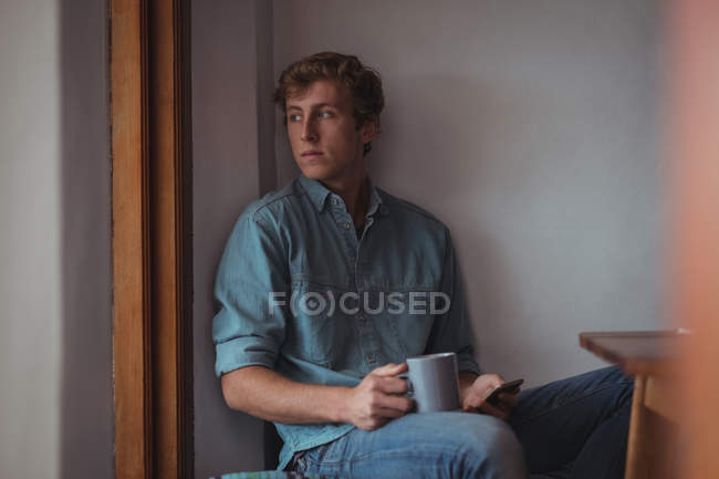 Thoughtful man holding a coffee cup at home — Stock Photo