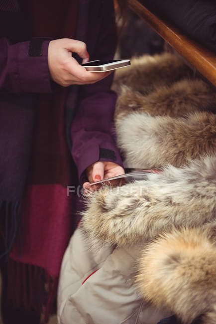 Close-up of woman taking photo of apparel using mobile phone in a clothes shop — Stock Photo