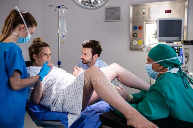 Доктор следственный беременной женщины во время родов во время человек, держащий руку в операционной комнате — стоковое фото