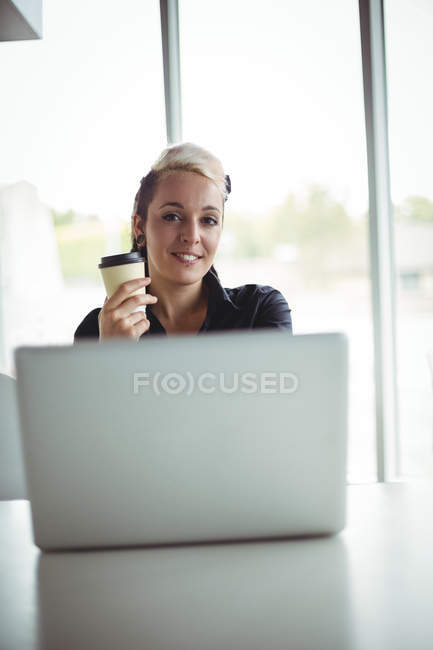 Portrait of woman holding disposable coffee cup in cafe — Stock Photo
