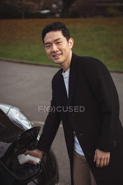 Portrait of smiling man charging electric car at electric vehicle charging station — стоковое фото