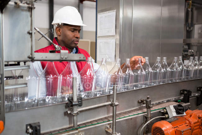 Confident male employee examining bottles in juice factory — Stock Photo