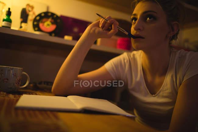 Frau denkt beim Schreiben von Notizen im Salon zu Hause — Stockfoto