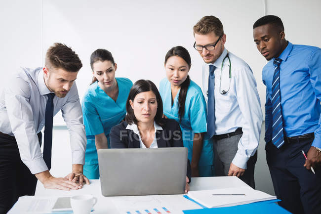 Team of doctor discussing over laptop in meeting at conference room — Stock Photo