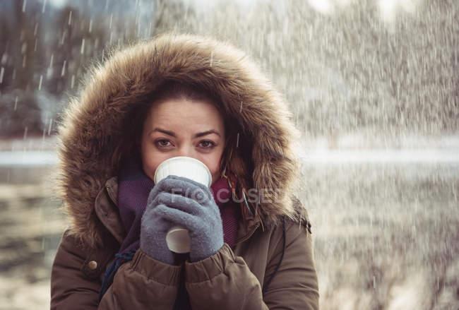 Ritratto di bella donna in pelliccia che beve caffè in inverno — Foto stock