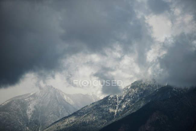 Vue tranquille des belles montagnes couronnées de neige et des nuages sombres — Photo de stock