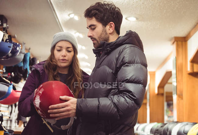 Couple selecting helmet together in a shop — Stock Photo