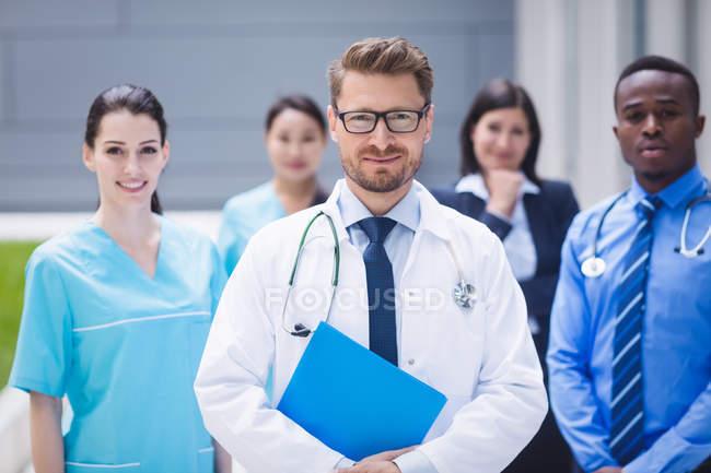 Retrato de sonriente médicos de pie juntos en instalaciones del hospital - foto de stock