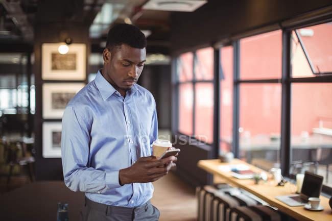 Бизнесмен, держа чашку кофе, одноразовые и с помощью мобильного телефона в офисе — стоковое фото