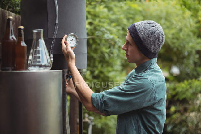 Man checking gauge while making beer at home brewery — Stockfoto