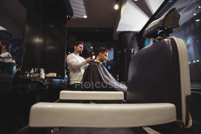 Barbier souffler séchage des cheveux du client dans le salon de coiffure — Photo de stock