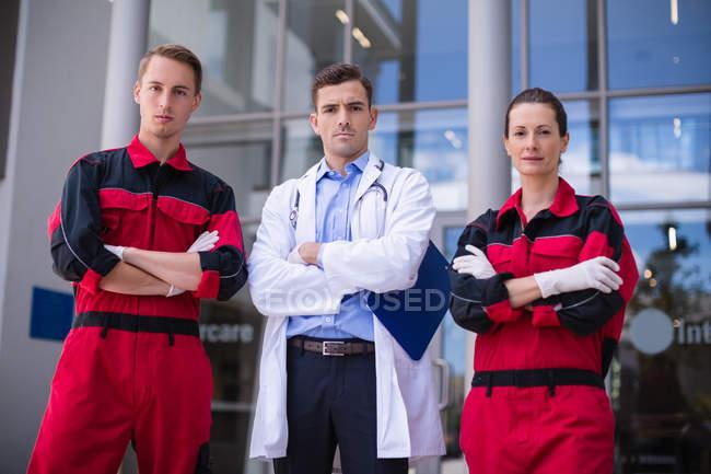 Retrato de médico e paramédico de pé com os braços cruzados no hospital — Fotografia de Stock