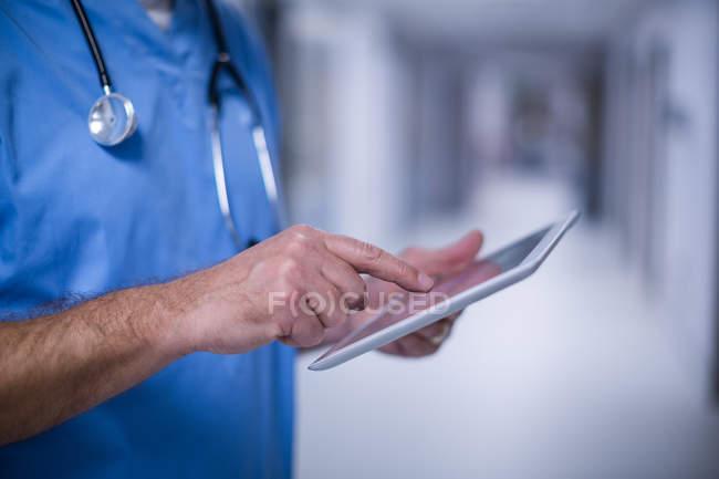 Средняя часть хирурга-мужчины с помощью цифрового планшета в операционной в больнице — стоковое фото
