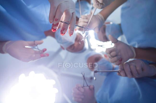 Grupo de cirurgiões que realizam operação em sala de operação no hospital — Fotografia de Stock