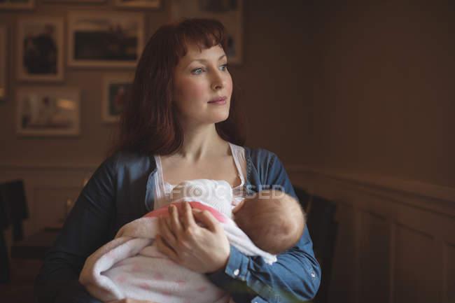 Madre in possesso di carino bambino figlia in armi a caffè — Foto stock