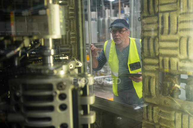 Employee watching machinery at juice factory — Stock Photo