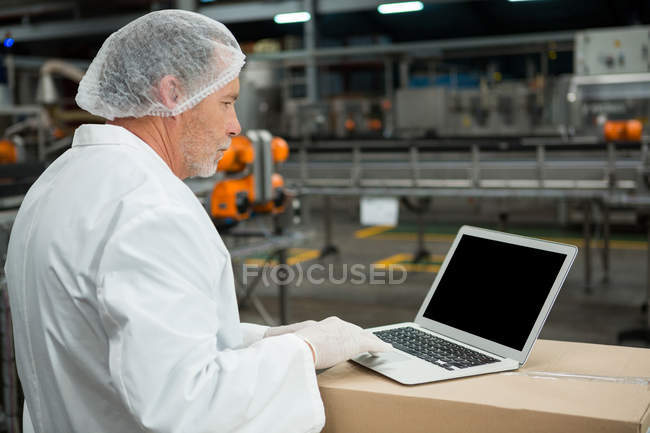 Side view of male worker using laptop in cold drink factory — Stock Photo