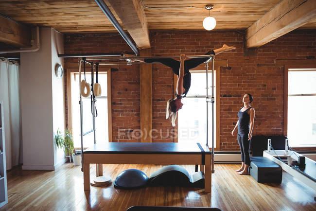 Тренер консультирует женщину во время занятий пилатесом в фитнес-студии — стоковое фото