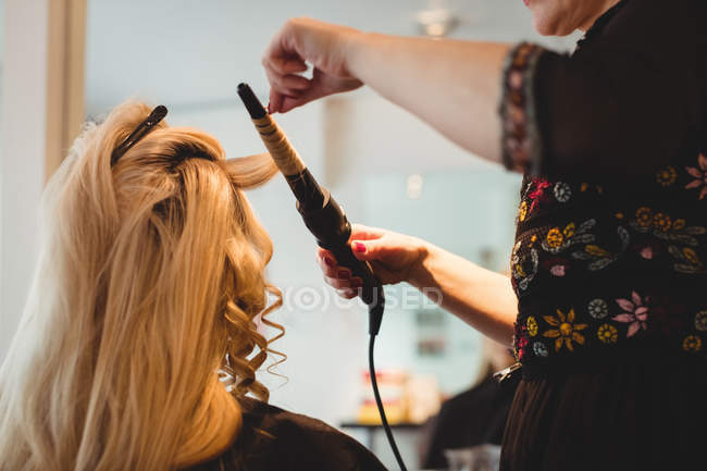 Close-up of female hairdresser styling clients hair in saloon — Stock Photo