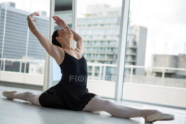 Ballerina performing a split in the ballet studio — Stock Photo