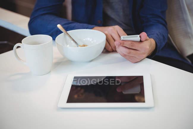 Людина, що використання мобільного телефону маючи сніданок кухні в домашніх умовах — стокове фото