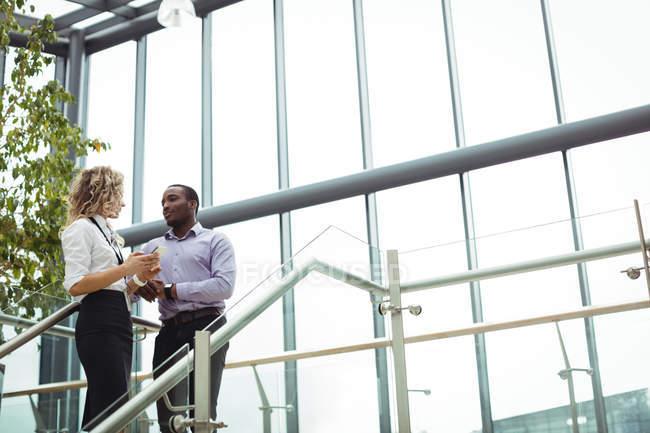Dirigeants d'entreprises discuter près d'escalier dans le couloir de bureau — Photo de stock