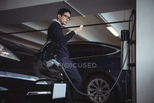 Homme à l'aide de téléphone portable pendant le chargement de la voiture électrique dans garage — Photo de stock