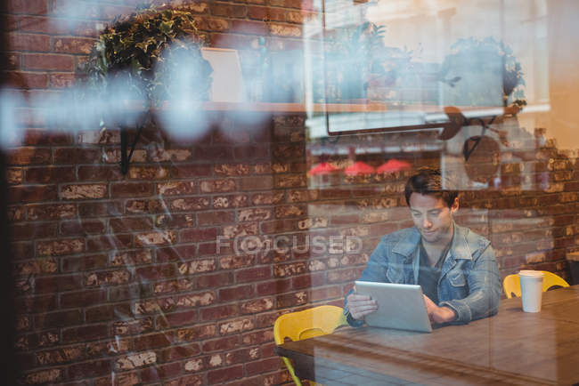 Man using digital tablet with coffee cup on table in cafe — Stock Photo