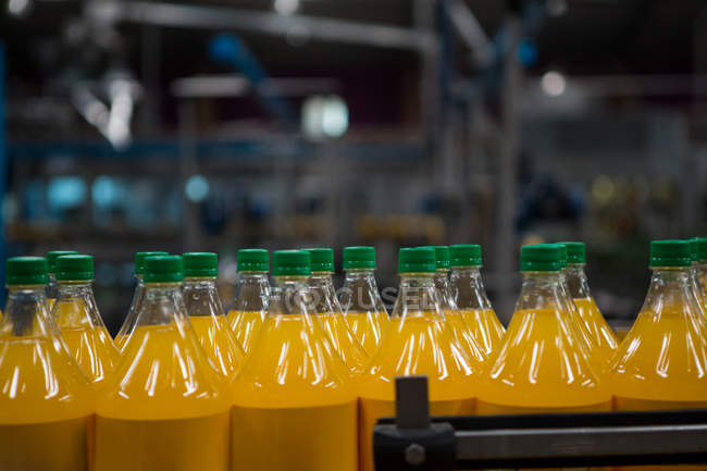 Close up of yellow juice bottles in factory — Stock Photo
