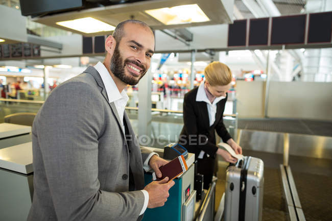 Smiling businessman standing with passport while attendant sticking tag to luggage in airport terminal — Stock Photo