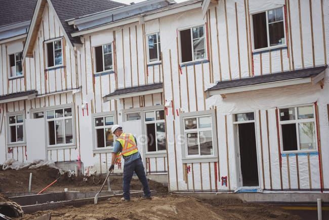 Строители выравнивают грязь на строительной площадке — стоковое фото