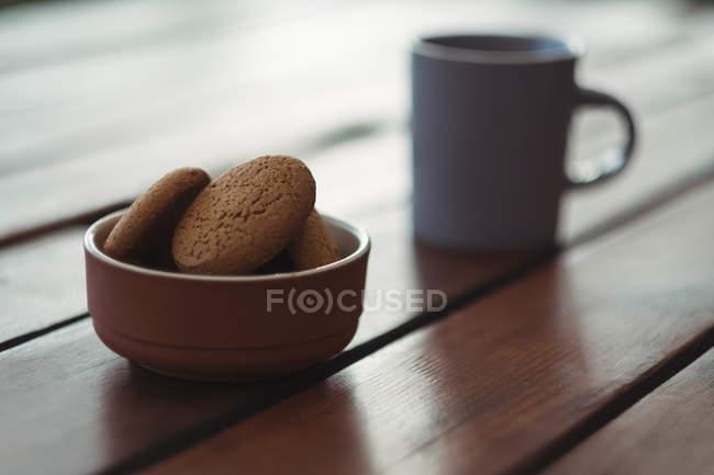 Primo piano dei biscotti in ciotola sulla scrivania con la tazza di caffè — Foto stock
