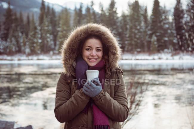 Vista frontale della bella donna in cappotto di pelliccia che tiene tazza di caffè in inverno — Foto stock