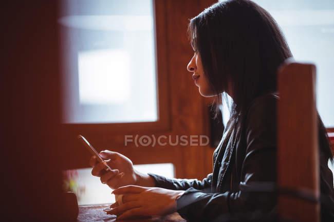 Femme utilisant un téléphone portable tout en prenant une tasse de café au café — Photo de stock