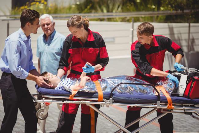 Paramédicos examinando menino ferido na rua — Fotografia de Stock