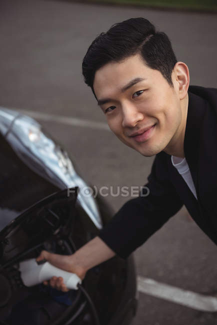 Portrait of man charging car at electric vehicle charging station — Stock Photo