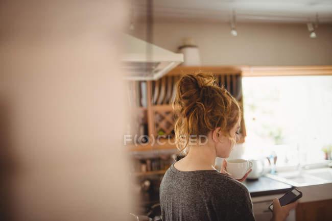 Frau benutzt Handy in Küche zu Hause — Stockfoto