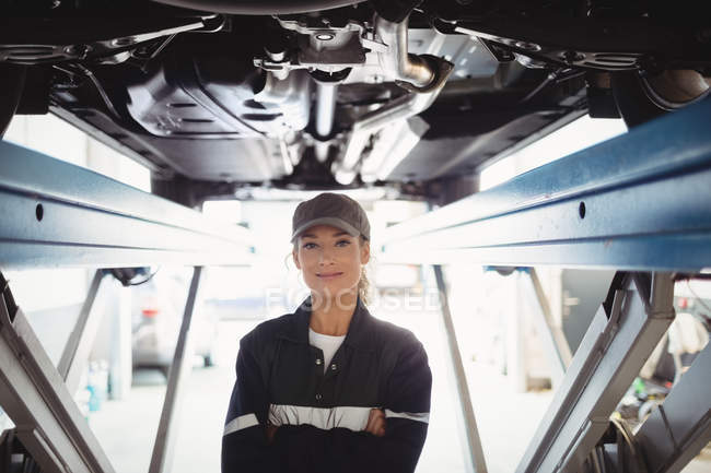 Female mechanic standing with arms crossed under a car in repair garage — Stock Photo