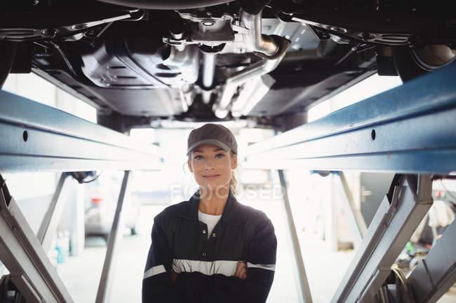 Weibliche Mechaniker stehend mit Arme gekreuzt unter einem Auto in der Werkstatt — Stockfoto