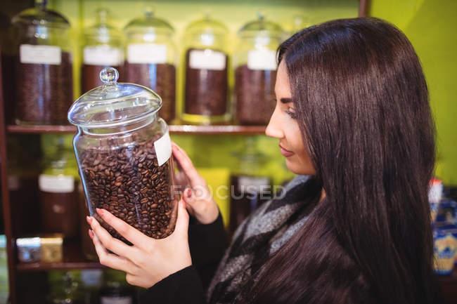Hermosa mujer sosteniendo frasco de granos de café en el mostrador en la tienda - foto de stock